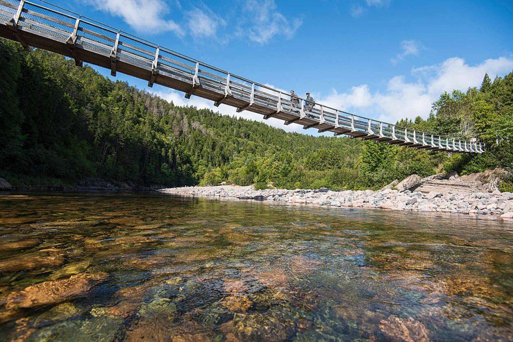Randonneurs sur le pont suspendu traversant la rivière Big Salmon